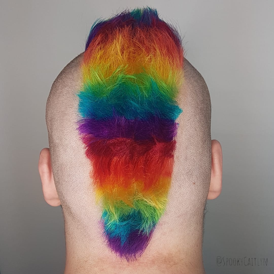 Back view head shot of a male model with rainbow color hair cut