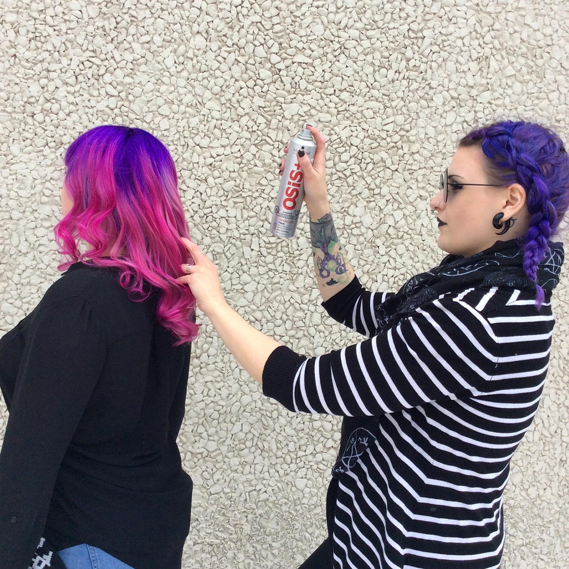 Stylist spraying hair of female customer