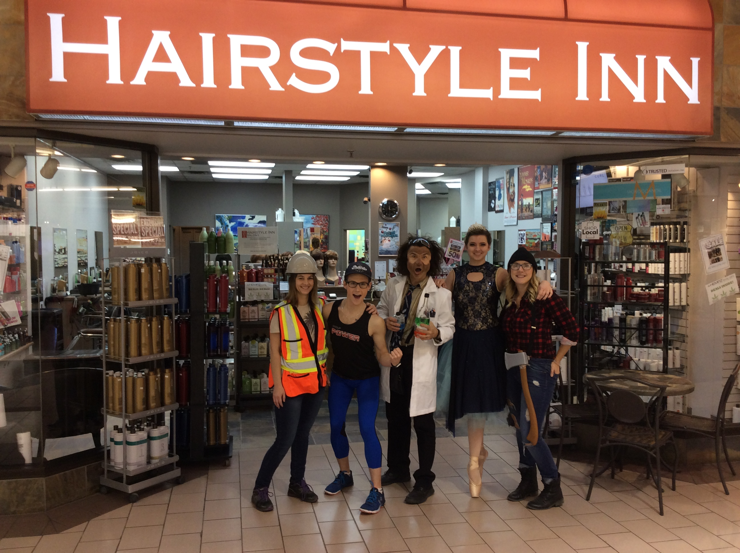 Hairstyle inn team dressed in Halloween costumes at the salon's entrance