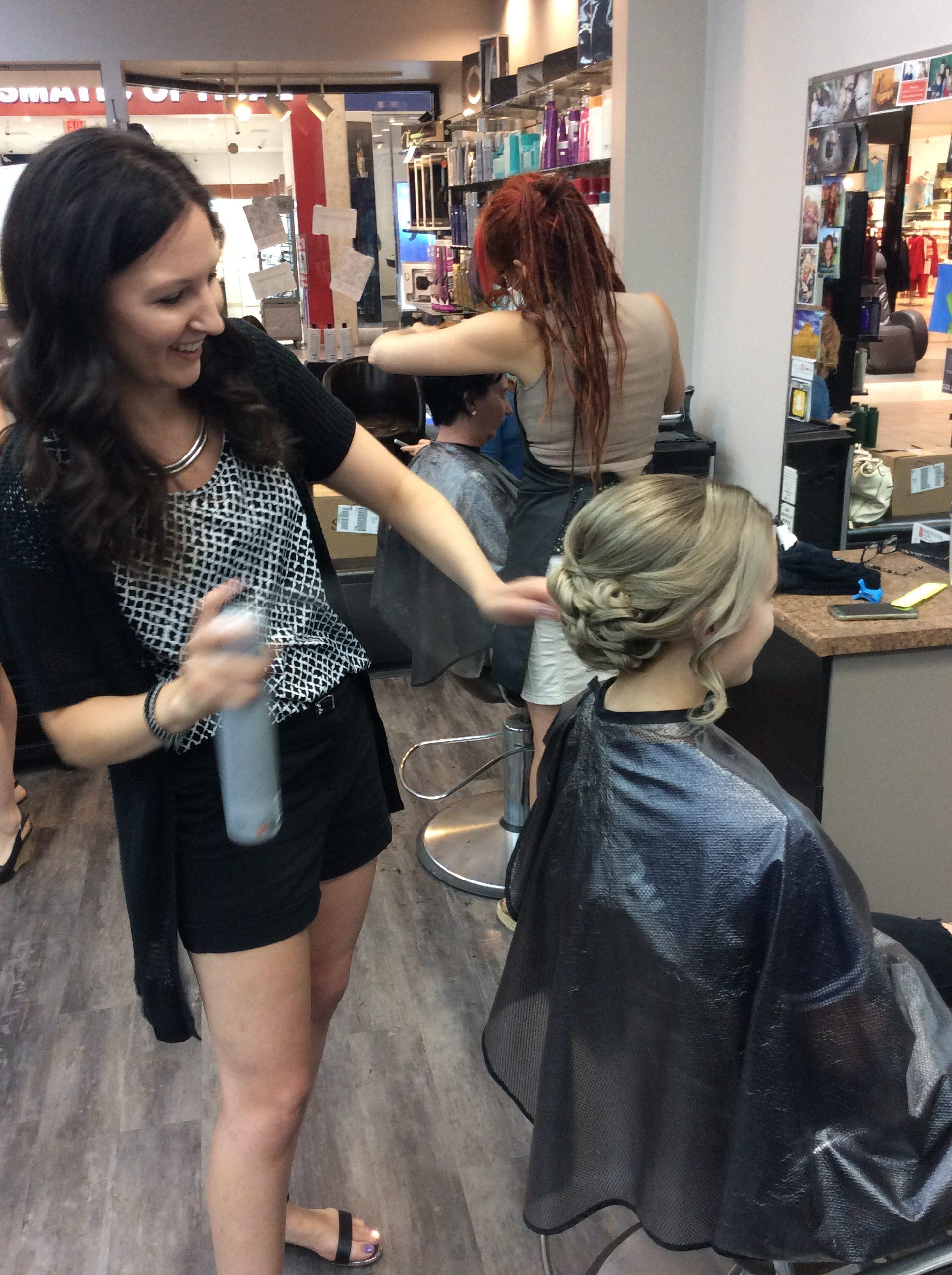Hairstyle inn stylist applying hair spray to a female customer's hair-do
